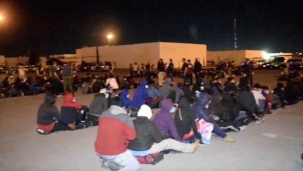 Мигранты сидят на земле после того, как иммиграционные власти вывели их из грузовиков в Сьюдад-Виктория, Тамаулипас, Мексика, 8 октября 2021 г. (Tamaulipas Public Safety Secretariat Handout via AP/Screenshot via NTD)