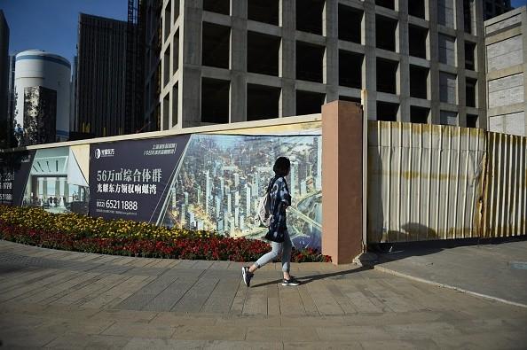 Женщина проходит мимо пустых зданий в Конч-Бэй, напротив нового финансового района Юйцзяпу в Тяньцзине, на севере Китая, 14 мая 2015 г. (Грег Бейкер / AFP через Getty Images)   Epoch Times Россия