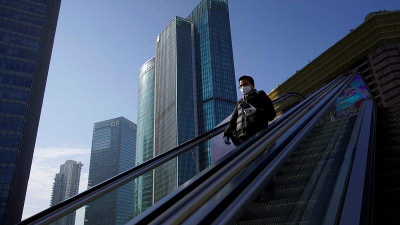 Мужчина в маске едет на эскалаторе в финансовом районе Луцзяцзуй в Пудуне, Шанхай, Китай, 10 февраля 2020 г. (Aly Song/Reuters) | Epoch Times Россия