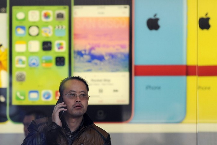 Китаец звонит по мобильному телефону в магазине Apple в Пекине 17 января 2014 года.  Фото: WANG ZHAO/AFP/Getty Images