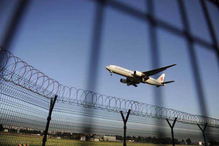 Самолёт Air China идёт на посадку в международном аэропорту Пекина 4 сентября 2012 года. Китай переживает отток активов предпринимателей, желающих хранить деньги в более безопасных местах. Фото: WANG ZHAO/AFP/GettyImages