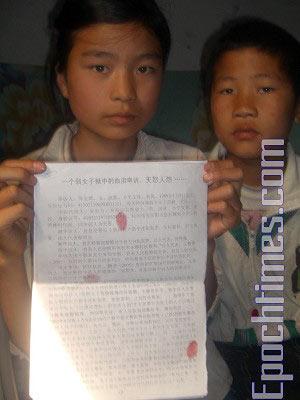 Брат и сестра держат письмо, в котором они взывают к правосудию. Фото: Великая Эпоха
