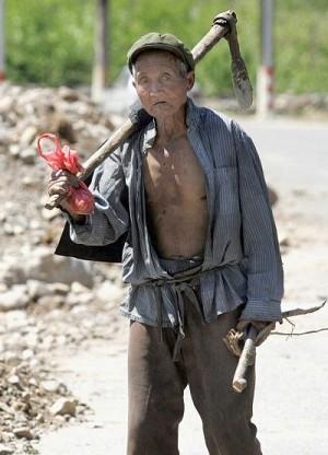 Пожилой китайский крестьянин бредет по дороге в предместьях Пекина. Тысячи безземельных крестьян в Китае требуют соблюдения их прав, утверждая, что китайский коммунистический режим считает Олимпийские Игры 2008 года в Пекине намного более важными, чем их благосостояние. Фото: STR/AFP/Getty Images