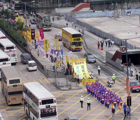 Парад шествует по Монкок, по обеим сторонам улицы стоят жители и туристы, которые наблюдают за грандиозным парадом. Фото: Цзинчао Пань/Великая Эпоха