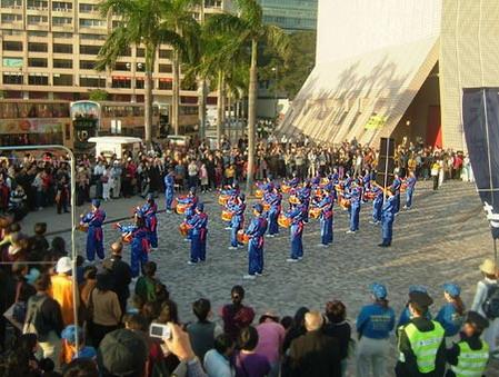 Барабанщики, участвующие в шествии, выбивают барабанную дробь. Среди них почти все люди, совершенствующиеся по древней духовной системе Фалуньгун. Многие их них пострадали от преследований и репрессий со стороны КПК. В Китае репрессии не