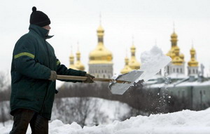 Муниципальный служащий убирает снег около Киевско-Печерской лавры. Фото: SERGEI SUPINSKY/AFP/Getty Images