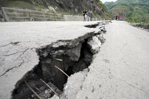 В результате землетрясения раскалывался асфальт, много дорог засыпано камнями и невозможно добраться до терпящих бедствие. Фото: LIU JIN/AFP/Getty Images