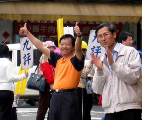 Наблюдавший за митингом гражданин поднимает большие пальцы вверх, выражая свою полную поддержку. Фото: minghui.ca