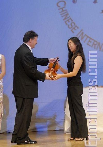 Член жюри Лойс Лев (Louis Lev) вручает особый приз «восходящей звезды» – скрипку ручной работы, конкурсантке № 9 Ли Юаньси. Фото: Даи Бин/ The Epoch Times