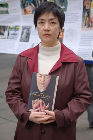 Дженнифер Цзен держит в руках автобиографическую книгу «История свидетеля», в которой описаны пережитые ею события в Китае - она подверглась репрессиям за то, что занимается Фалуньгун. Фото: The Epoch Times