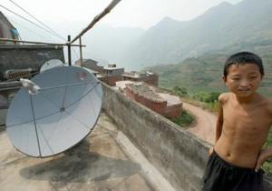 Маленький китайский мальчик стоит на крыше своего дома у спутниковой тарелки в новой деревне мигрантов Гуйхуа.  Семьи подобные его, с 16 июня лишились возможности принимать сигнал ТВ НДТ. Фото: Goh Chai Hin/AFP/Getty Images