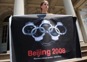 Женщина держит плакат с изображением олимпийских колец в виде наручников во время демонстрации в защиту прав человека в Китае, на ступеньках здания городского совета Нью-Йорка. Фото: Don Emmert/AFP/Getty Images