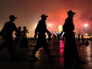 Служащие китайской службы безопасности патрулируют у олимпийского стадиона «Птичье гнездо» в Пекине. Фото: Frederic J. Brown/AFP/Getty Images
