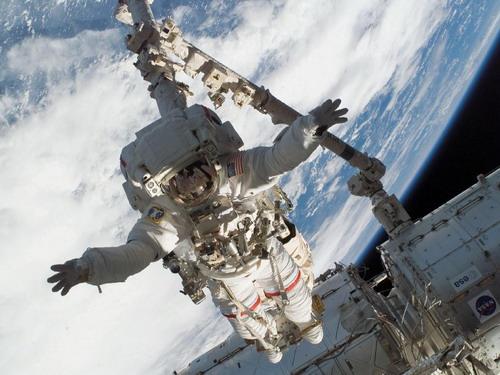 """Поставленный на космический якорь Canadarm2, астронавт Rick Linnehan участвует в первом запланированном выходе в открытый космос. Во время семичасового выхода в открытый космос Linnehan подготовил к установке японский модуль """"Кибо"""". Фото: С сайта nasa.gov"""