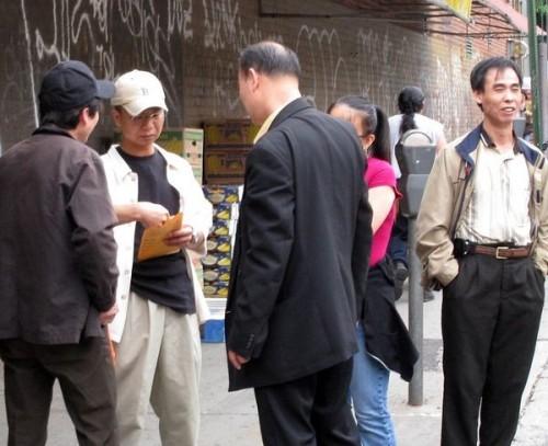 Неподалёку от места событий – района Flushing, неизвестный китаец в костюме выдаёт деньги активным участникам группы поддержки компартии. Фото предоставлено жителем Нью-Йорка