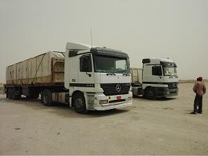 Два индийских водителя со своими грузовиками во время отдыха в кувейтской пустыне перед пересечением границы Ирака