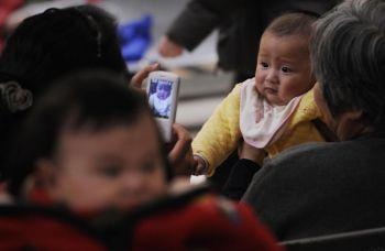 Родители со своими детьми в пекинской больнице. Фото: Peter Parks/AFP/Getty Images