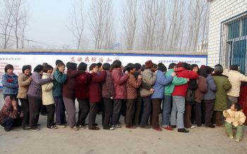 Жители деревни Вэньлоу провинции Хэнань, которых заразили ВИЧ-инфекцией, когда они в качестве доноров, сдавали кровь за деньги, стоят в очереди за получением лекарства. Фото: STR/AFP/Getty Images
