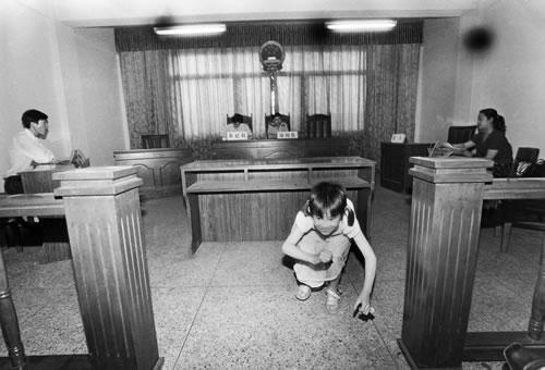 Пока муж с женой оформляют развод в суде, их ребёнок нашёл себе развлечение. Фото: Великая Эпоха.