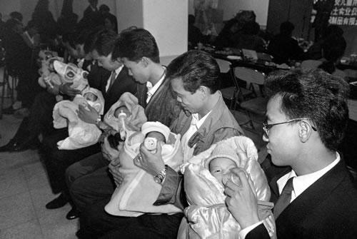 Молодые папы учатся кормить детей молоком. Фото: Великая Эпоха.