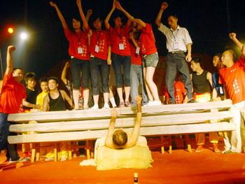 Мастер жёсткого цигун Ли Пэнфэй удерживает на груди вес массой 2 тонны. Фото с epochtimes.com