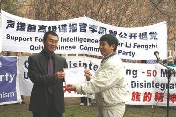 Руководитель Всемирного Центра   помощи выхода из компартии, доктор наук Гао Давэй (справа) вручает Ли Фэнчжи   документ центра, подтверждающий его выход из рядов КПК. Фото: Си Мин/The Epoch Times
