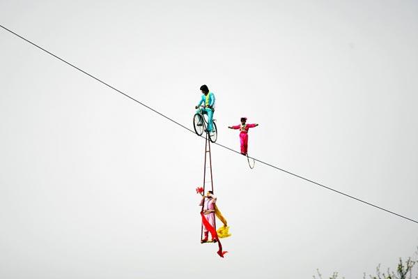 Позади велосипеда по канату идёт 6-летняя девочка. Ботанический парк в Шанхае. 1 марта. Фото с сайта epochtimes.com