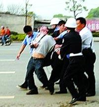 Полицейские и городские контролёры грубо арестовывают корреспондента Чена Юна. Фото   сделано местным жителем с помощью мобильного телефона