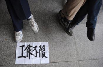 Китайские рабочие ищут работу. Надпись на объявлении: «Ищу любую работу». Фото: China Photos/Getty Images