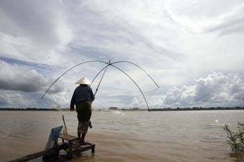 Женщина ловит рыбу в Такхеке в Лаосе. Фото: Hoang Dinh Nam/AFP/Getty Images