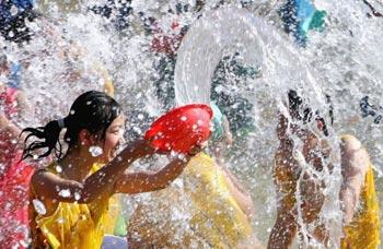Праздник воды народности дай в Китае. Участники обрызгиваются водой. Фото: Guang   Niu/Getty Images