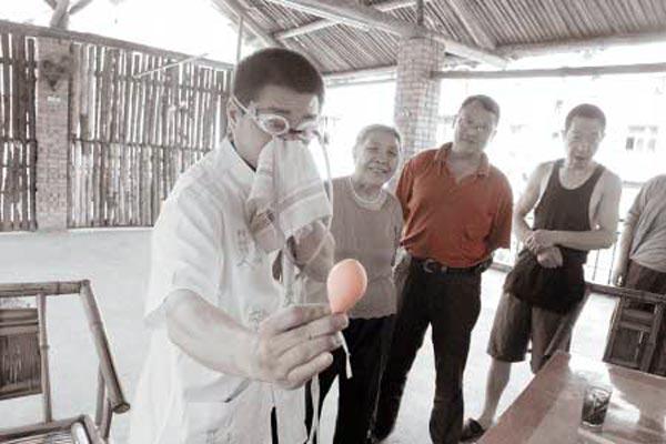 Чжан Цзюю глазом надувает воздушный шар. Фото с epochtimes.com