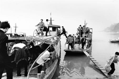 Пассажиры перегруженного катера выходят на берег. Провинция Сычуань. 2000 год. Фото: Yang Hui