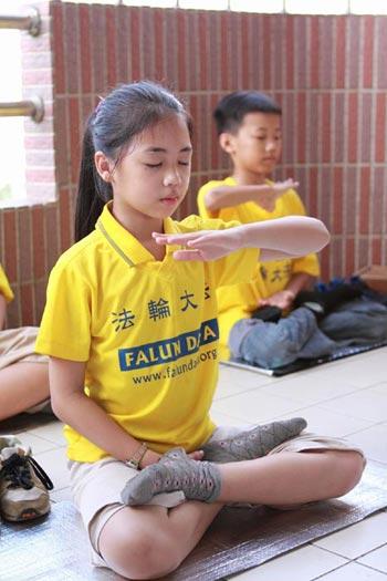 Юные практикующие выполняют упражнения Фалуньгун. Фото с faluninfo.ru