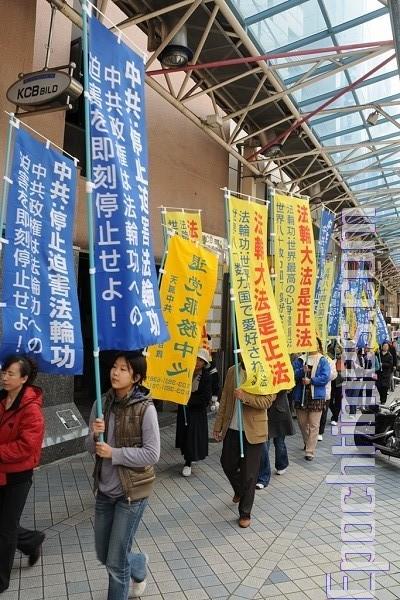 Жители и гости города интересуются происходящим, читают информационные материалы. Фото: Hong Kazuo/The Epoch Times