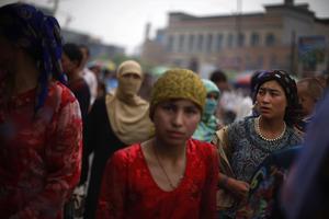 Уйгурка на базаре в Хотане 12 июля. Силы безопасности все еще находятся  в «высокой степень готовности». AP Photo/Elizabeth Dalziel