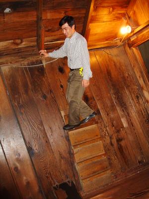 Идти вверх по стене? В деревянном домике в «Мистической зоне» для этого достаточно нескольких узких планок на стене и загадочно измененной силы притяжения, так что каждый участник легко может проделать это. Фото: Катарина Фолькерс /Великая Эпоха