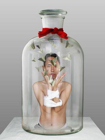 Человек в бутылке, 2009. Фотомонтаж: Запертый в бутылке художник Норцзе (1963 г.р.) Из перевязанных рук он выпускает в пространство бутылки бабочек с тибетскими письменами! Горлышко бутылки перевязано красной лентой. Указание на красный галстук пионеров - молодежной организации компартии? (Норцзе) Фото: Великая Эпоха (The Epoch Times, Германия)
