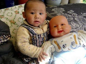 Маленький ребенок с китайской куклой, 2009 художника Kelsang Tsering (1969 г.р.) По традиции в Тибете нет специальных игрушек и кукл для детей. Кукла младенец сделана в Китае и, очевидно, предназначалась для западного рынка. (Келсанг Тзеринг) Фото: Великая Эпоха (The Epoch Times, Германия)