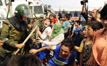Китайский полицейский готов ударить уйгурскую женщину за её протест в Урумчи, провинции Синьцзян, на дальнем западе Китая. 7 июля 2009 года. Фото: Peter Parks /AFP /Getty Images