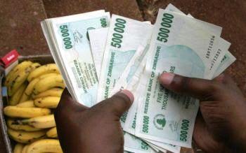 Житель Зимбабве отсчитывает пачку купюр для того, чтобы купить несколько бананов. Продолжающийся экономический кризис привёл к самому высокому уровню инфляции в мире. Фото: Alexander Joe/AFP/Getty Images