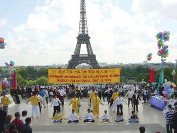 Последователи популярной во всем мире школы Фалуньгун выполняют коллективные упражнения перед Эйфелевой башней в Париже, которой исполнилось 120 лет. Фото: С сайта minghui.org