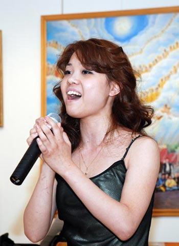 Вероника, последовательница Фалуньгун, исполняет песню на открытии выставки. Фото: Юлия Цигун/Великая Эпоха