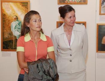Татьяна Сигалина, организатор выставки в Санкт-Петербурге (справа), рассказывает   посетительнице о картинах. Фото: Юлия Цигун/Великая Эпоха