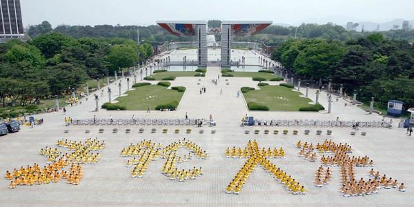 Около тысячи последователей Фалуньгун, одетые в жёлтые одежды, сформировали надпись на китайском языке «Фалунь Дафа». Сеул (Южная Корея). Фото с minghui.org
