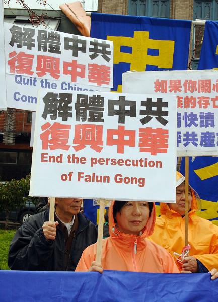Надписи на плакатах: «Выходите из КПК», «Положить конец преследованию Фалуньгун». Фото: Великая Эпоха