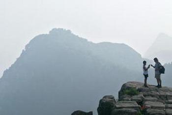Фото: Отец и сын перед горой Тайшань, самой знаменитой из пяти китайских священных гор даосизма в провинции Шаньдун. Frederic J. Brown/AFP/Getty Images