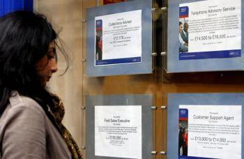 Женщина смотрит на рекламные объявления о работе.Фото: Paul Ellis/AFP/Getty  Images