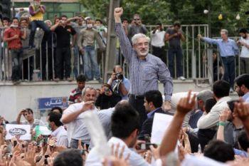 Потерпевший поражение кандидат в президенты от реформистов Мир-Хусейн Муосави (С) виден с поднятой рукой на уличной демонстрации 15 июня 2009 года в Тегеране, Иран. Фото: Getty Images