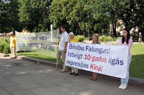 Практикующие держат плакаты, призывающие остановить преследование Фалуньгун в Китае